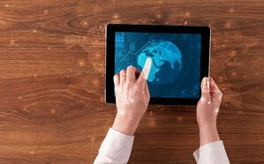 Hand touching tablet with worldwide reports links and statistics concept